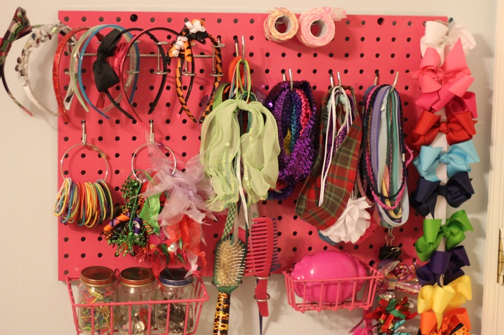 The pegboard organizer for my daughter's hair stuff I just made. Board and wire bins spray painted pink.