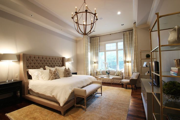 Elegant bedroom features tray ceiling accented with iron and rope chandelier hanging over brown tufted bed dressed in white linen bedding flanked by black nightstands topped with tapered glass lamps as well as French bench placed at the foot of the bed atop cream and gold Persian rug.