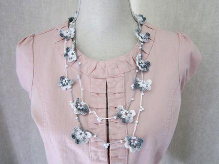 Joli sautoir parsemé de fleurs grises-blanches dégradées, ainsi que de nombreuses perles blanches. Ce collier comporte 2 rangs (reliés ensemble). Il est réalisé en coton fin - 20529940