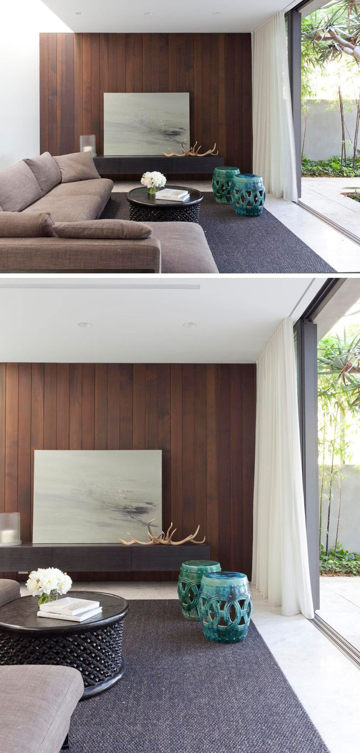This living area has a dark timber feature wall and siding glass doors that open up onto a private courtyard.