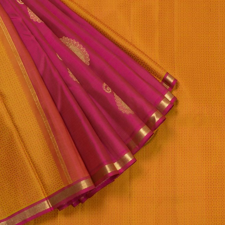 "The ""#Orange"" #handwoven #Kanjivaram #Silk #Sari from Kanakavalli is woven with diamond bhutas all over the body that is set off by a pink with gold zari border on either side. A section of pink with gold zari paisleys make up attractive pleats. An attractive gold zari adorn the pink pallu. The border is repeated on the pink blouse that completes the sari."