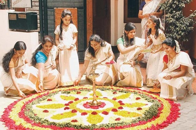 """Ladies busy preparing the """"Flower Rangoli"""" on the occasion of Onam."""