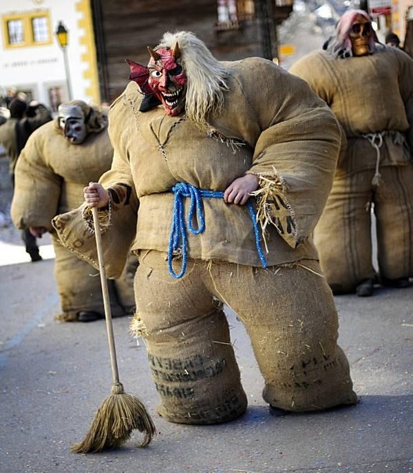 Empailles (Straw man) wearing a costume made of a jute bag stuffed with straw and scary mask walk through the streets of Evolene during a traditional carnival procession March 6, 2011. Empailles along with Peluche who wear costumes made of animal skins and masks invade the streets of the village and scare residents with their broomsticks or their bells during carnival.
