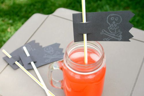 Using a black paper rectangle, cut 2 holes into the paper and slip it on the straw. You can decorate your drink flags with a skull sticker or use a white crayon.