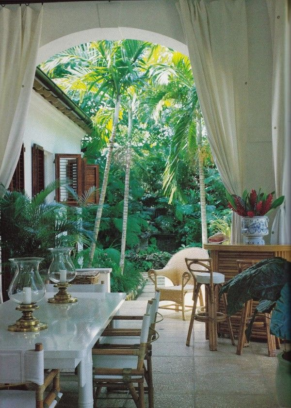 In a photo taken in 1984 of Ralph Lauren's veranda at Round Hill, Jamaica, a white lacquer bamboo dining table is surrounded by McGuire dini...