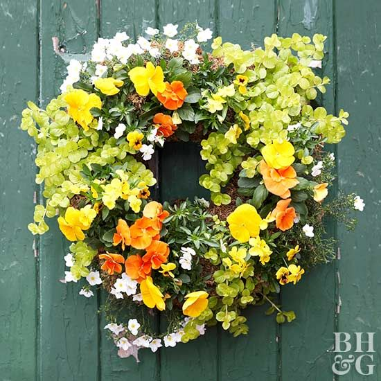 Citrus-color violas complement this wreath's dominant bright orange and yellow pansies.