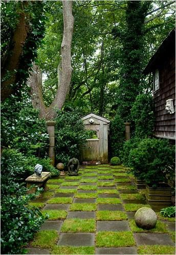 Awesome ground covering! Love the contrast between the square paving stones and the round stones and topiary.