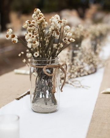 Casual Centerpiece- Cream and white dried ammobiums are set in Mason jars that are tied with twine for a down-home look.