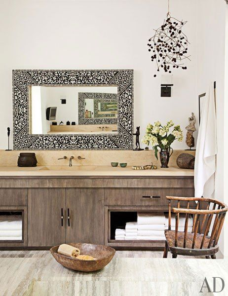 Elegant surfaces predominate in the master bath, with stained-walnut vanities, limestone countertops, and a marble floor; the mirrors with mother-of-pearl inlay are from India, the mobile is by Kevin Inkawhich, and the bronze cat sculpture is by Diego Giacometti.