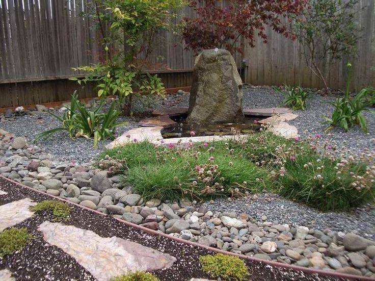 rocaille jardin japonais esprit zen avec fontaine en roche et clôture brise-vue en bois