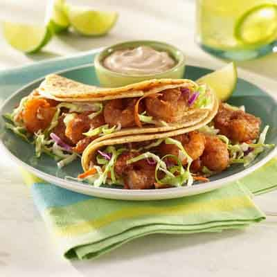 Spice-coated shrimp are baked and then placed on top of corn tortillas. Add coleslaw mix and drizzle them with a flavorful sauce for a new twist on tacos.