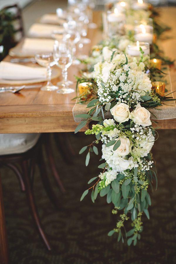 Une table en bois brut joliment accessoirisée d'un chemin de table en fleurs blanches, pour la rendre chic et romantique.