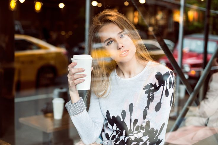 Must have: Beautiful caucasian woman sitting in city coffee shop near the window, drinking coffee from paper.