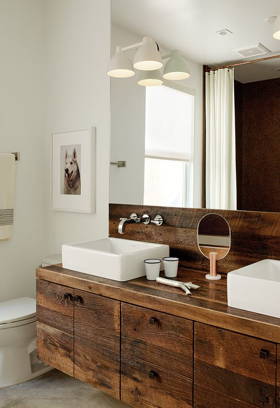Builder Luke Gilligan of Gilligan Development used reclaimed oak planks from a deconstructed barn to create the bathroom's millwork. To achieve the rugged look, he sanded and wire-brushed the wood, then applied a clear stain. The sinks are from Duravit's Vero line and the cabinet pulls are from Top Knobs.