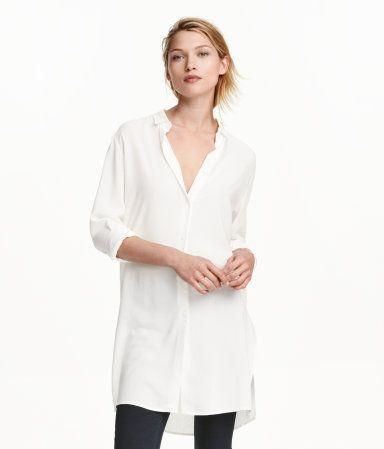 Weiß. Lange, gerade geschnittene Bluse aus leichtem Viskosestoff. Die Bluse hat einen schmalen Kragen und Knöpfe vorn und an den Ärmeln. Seitliche Schlitze.