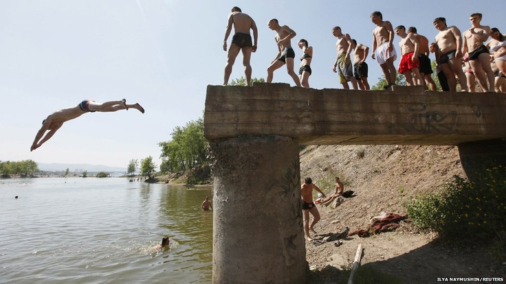 People queue to jump in to the Yenisei River