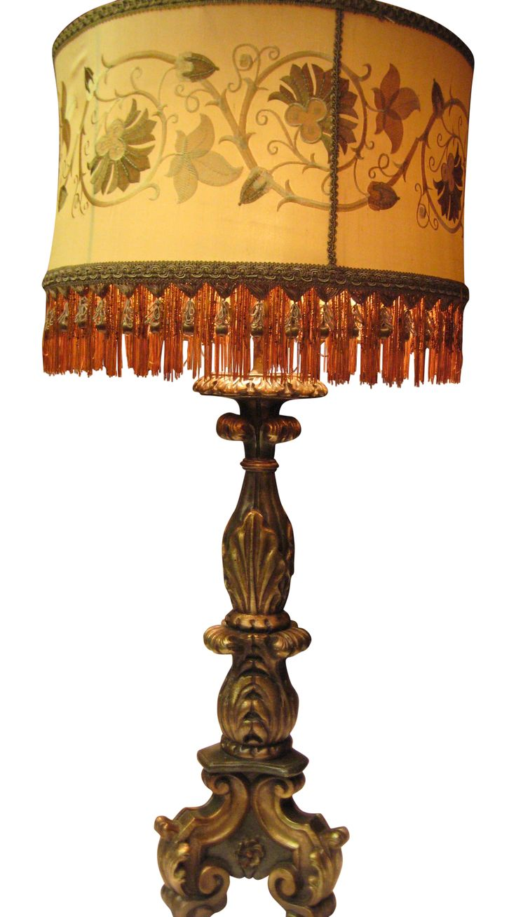 A large Mediterranean table lamp with an embroidered silk lamp shade in cream color with green embroidered designs. The base is a green and gold ornate column with an antique finish. It's in excellent condition considering it's age.