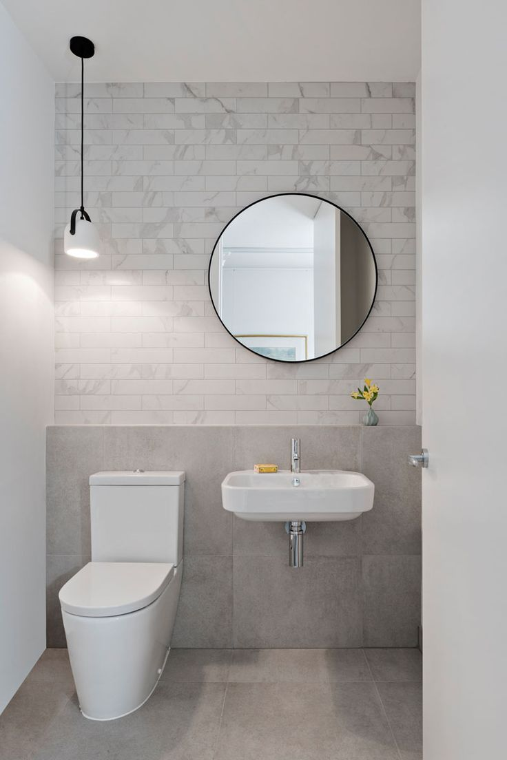 White and light grey tiles line the back wall in this modern bathroom, while a single white and black pendant light hangs above the toilet.
