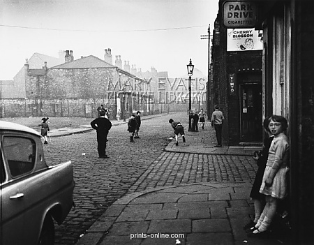 Playing cricket in the street - Salford 1962.  A group of boys play a game of cricket in this Manchester street, using a lampost as the set of stumps. Two girls close to the camera stand in a doorway to watch proceedings. Photograph by Shirley Baker Copyright ©  Mary Evans Picture Library 2008