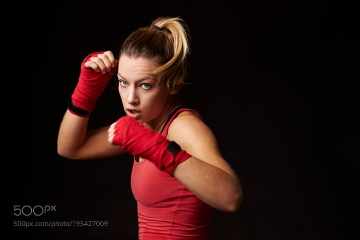 Young blonde woman shadow boxing in a blocking position by GuerillaProductions Young blonde woman shadow boxing in a blocking position