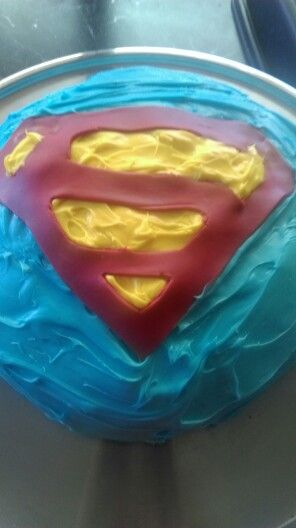 Superman birthday cake  Chocolate fudge cake with blue butter frosting, rolled red royal icing, with yellow butter frosting.