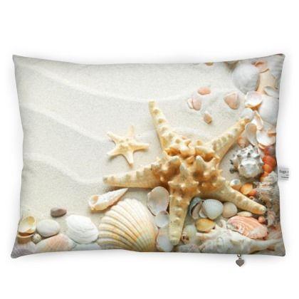 Cuscino con grafica stelle marine sulla spiaggia.