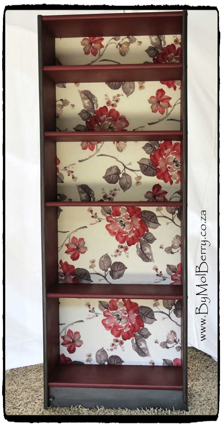 Refurbished bookcase in graphite and deep coral chalk paint with floral fabric baking.