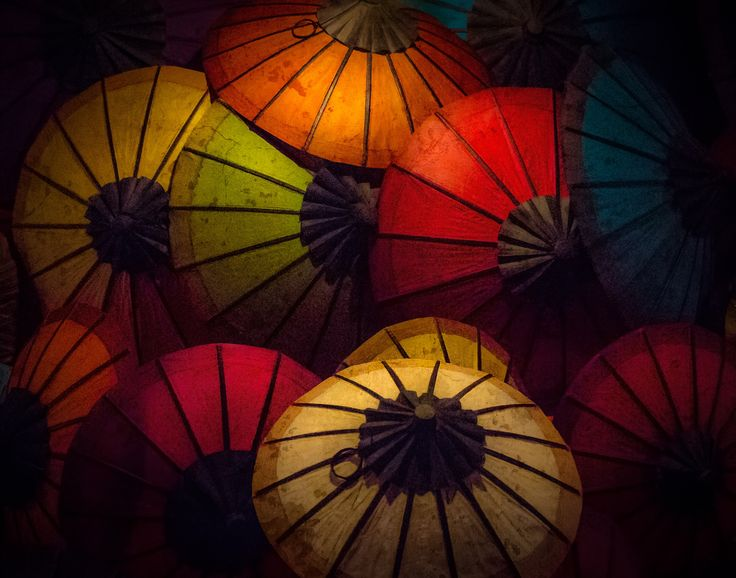 Umbrellas for sale - These umbrellas were resting on the sidewalk in the Chiang Mai night market in Thailand. The night was foggy and very humid and the umbrellas were lit by a single clear tungsten bulb hanging overhead