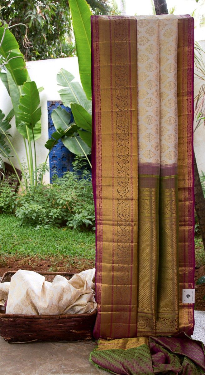 This ivory kanchivaram silk has traditional gold zari bhuttas all over the sari. The pallu and border are in green and purple with elaborate gold zari weaving making it the perfect choice for a spe...