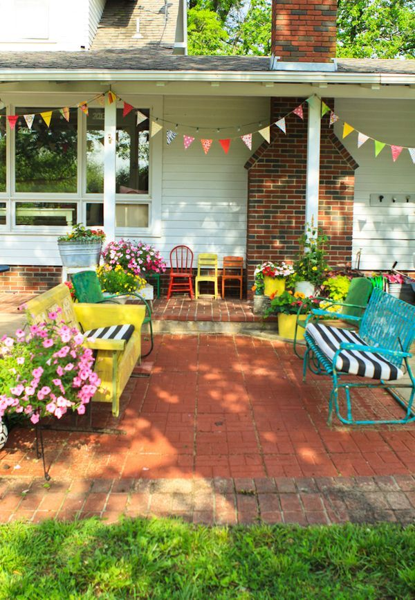 eclectic mix of outdoor furniture on a cute brick patio :: love the flower pots too.