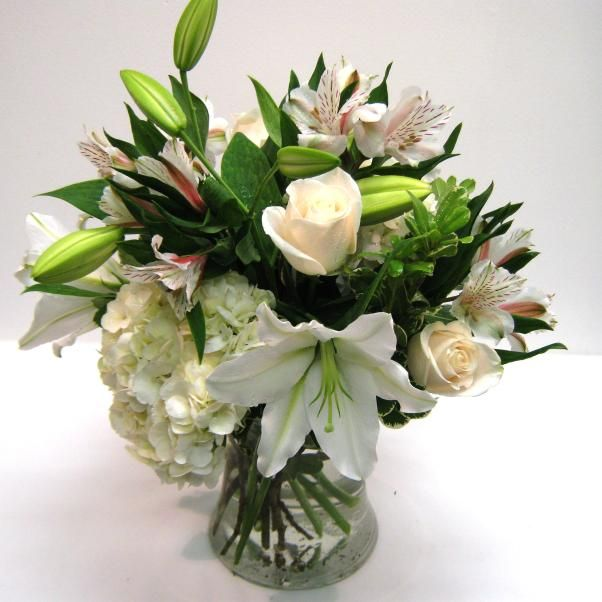 A clear glass vase with a bouquet of fragrant flowers in shades of white and cream for an elegant look.