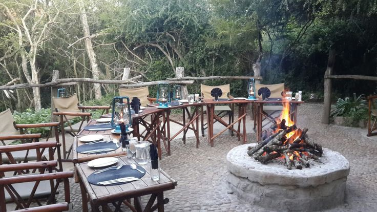 The boma area with fires roaring and set up for a traditional SA braai dinner in the bush at River Camp at Sibuya Game Reserve in the Eastern Cape of South Africa www.sibuya.co.za