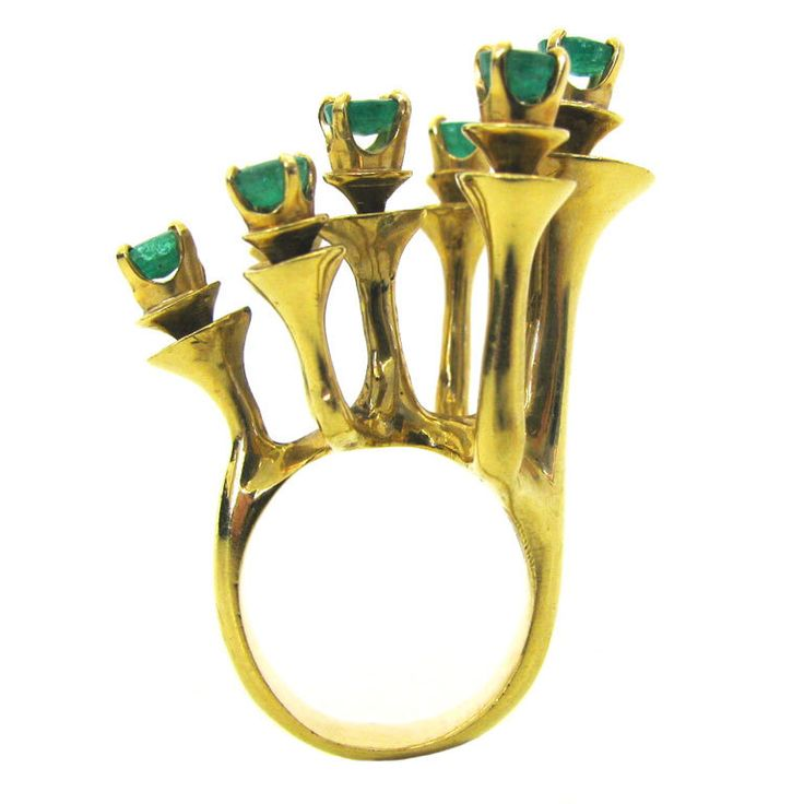 "Barbara Anton, A Modernist Gold and Emerald RIng c 1970  usa  c1970  A sculptural gold and emerald ring by Barbara Anton. The 1 1/4"" x 1"" 18k yellow gold ring made up of seven trumpeted pedestals each topped with a round faceted emerald. The ring extends 1"" high from the finger. A great pinky ring. Unsigned, from the Anton Estate. Stylish and dramatic. Size 5."