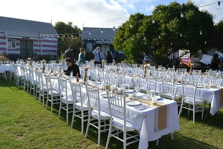 Outdoor wedding reception at the Beach Huts Middleton South Australia. Featuring chivari chairs, festoon lighting, lace and burlap table runners with twine bottles, hurrican lamps and love bird salt and pepper shakers.