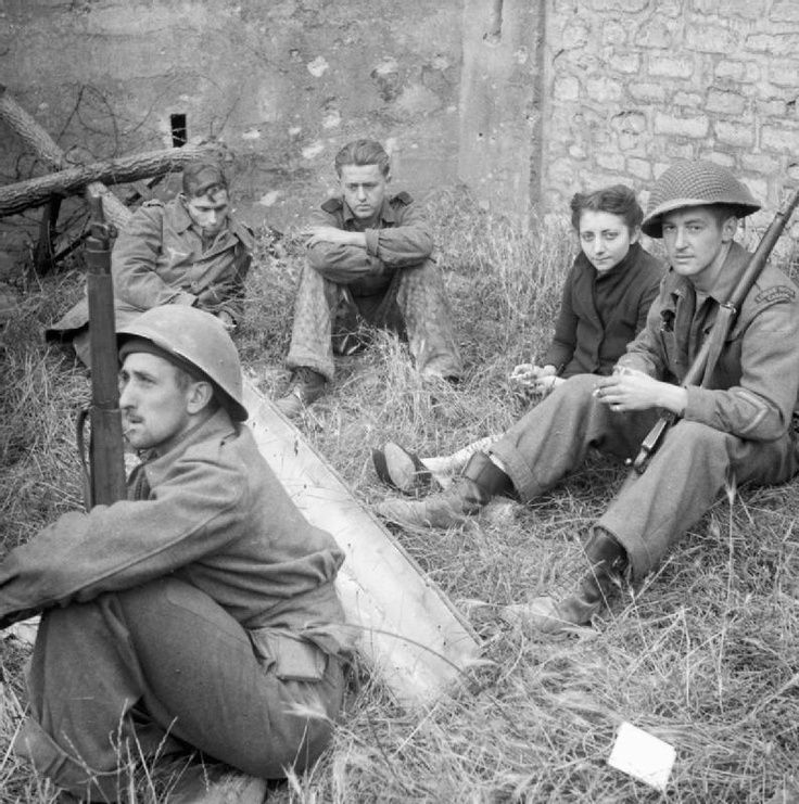 A French woman sits with German prisoners under Canadian guard on the outskirts of Caen, 19 July 1944.