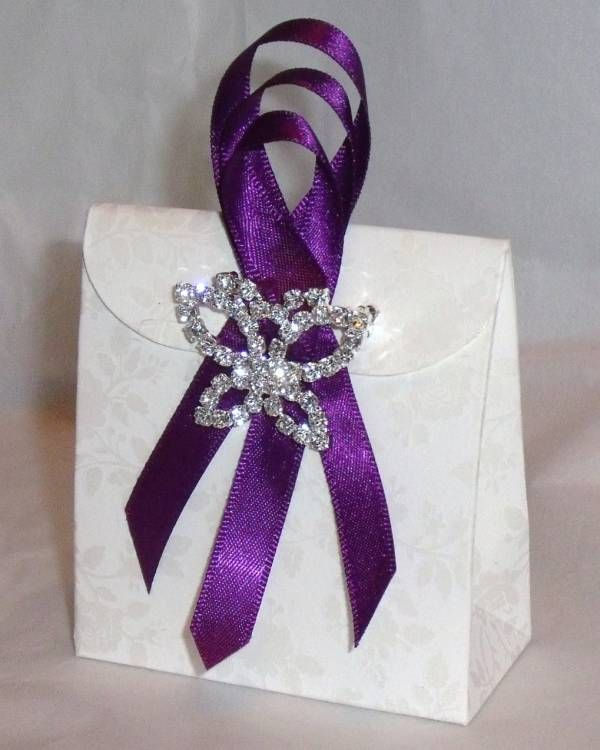Favor -A small off white floral embossed purse bag decorated with 3 loops of Cadbury's Purple satin ribbon finished off with a stunning diamante butterfly ribbon buckle and filled with tissue paper and 5 superior sugared almonds.  The butterfly is actually a brooch pin so will have a dual purpose, your guests will not only have a beautiful keepsake of your wedding but can actually wear it too!!