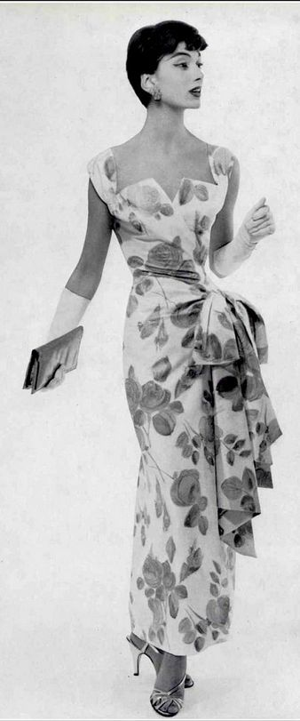 1955, Marie-Hélène in lovely cotton floral print evening dress gathered to one side at the hip in bow, by Jacques Griffe, photo by Guy Arsac