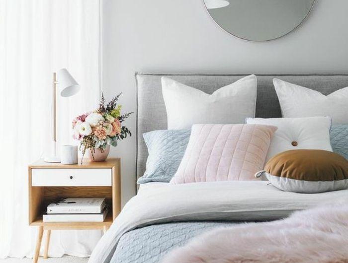 chambre rose et gris, miroir rond, coussins déco, chevet en bois, vases avec des fleurs
