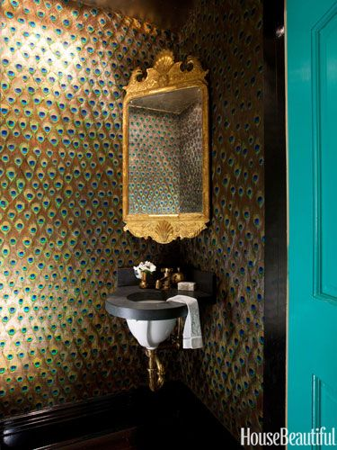 An antique Georgian mirror seems to float in a corner of the powder room, against the custom peacock-feather wallpaper.