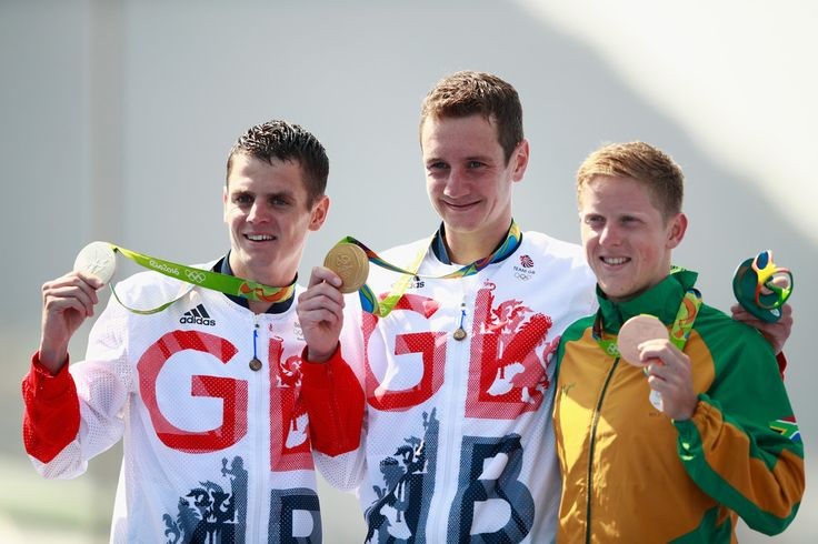 Gold medaltist Alistair Brownlee and silver medalist Jonathan Brownlee of Great Britain celebrate with bronze medalist Henri Schoeman of South Africa on the podium during the Men's Triathlon at Fort Copacabana on Day 13 of the 2016 Rio Olympic Games on August 18, 2016 in Rio de Janeiro, Brazil.