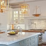Stunning two-tone kitchen design with gray kitchen island with marble & butcher block countertops, sink in kitchen island, creamy white shaker kitchen cabinets with polished black granite countertops, pot filler, marble slab backsplash and antique brass pendants.