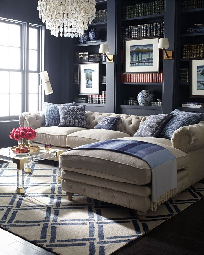 I can't get my eyes off this gorgeous library! The contrast between the tufted beige linen sofa and the dark navy built-in bookshelves are simply marvelous, drawing your eye to the lovely details of the beautiful sofa. I really like how the stylish acrylic and brass coffee table and the fabulous geometric rug are visua