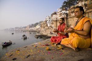 What to Know About India's Caste System: A Brahmin priest and his assistant pray beside the Ganges River.