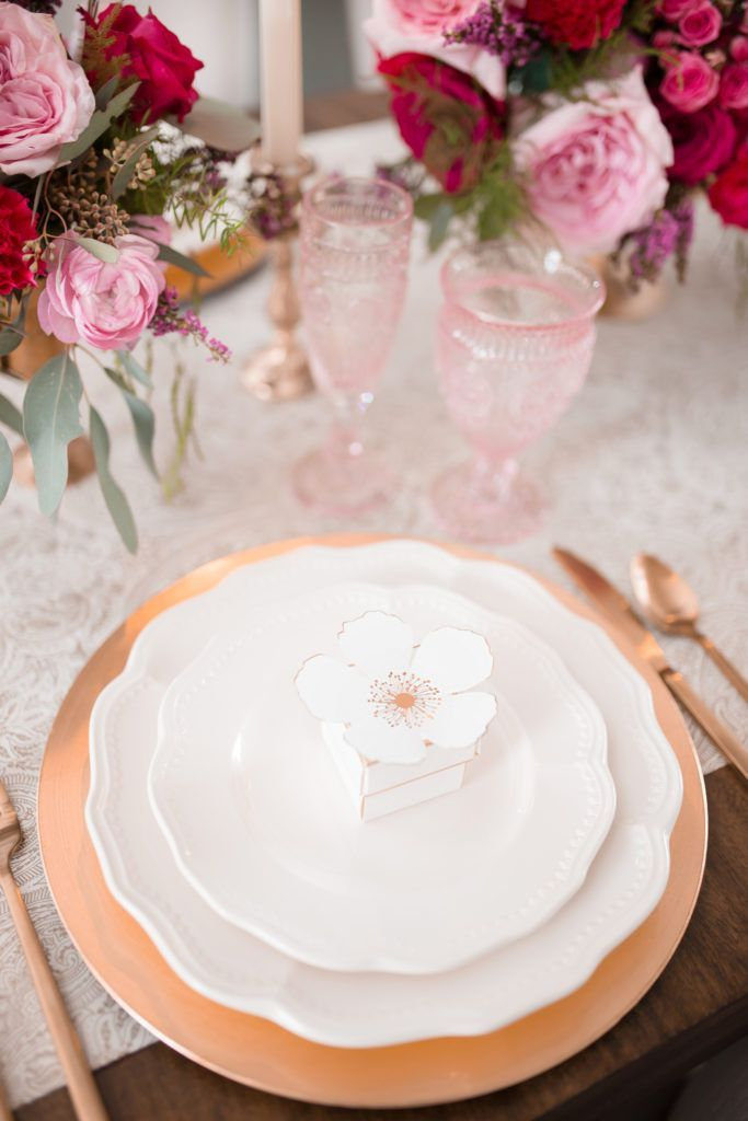 Choose your place settings for a romantic table carefully. I suggest using a metallic, like this gold charger, with neutral plates so that your other decor can do the work for your theme.
