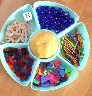 Crearemos un recipiente con diferentes piezas (números, botones, palitos de colores, canicas de colores) y en el centro del recipiente una bola de plastilina y 2 dados. Separaríamos la plastilina en 3 porciones. Lanzaríamos el dado una primera vez y en función del número se cogerán tantos objetos y se colocará en la primera porción. Idem con el otro dado. Por último se contarán los objetos de ambas porciones y se pondrán en la tercera