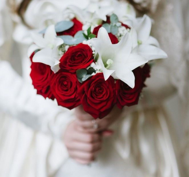 White lilies and red roses with eucalyptus and myrtle leaves