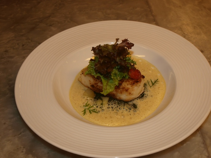 AUBERGINE - Pan seared Chilean sea bass served on a ragout of potato and spinach topped with petit salad greens and saffron-vanilla froth.