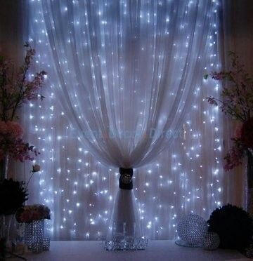 Strings of mini-lights attached to a rod behind sheer fabric.Beautiful