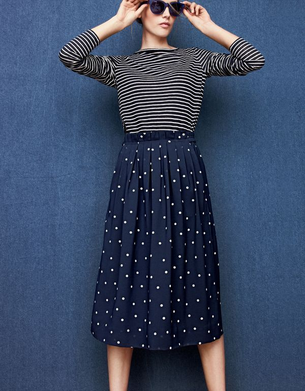 J.Crew women's linen long-sleeve striped T-shirt, pleated midi skirt in polka dot and Sam sunglasses.