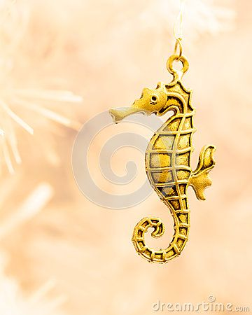 A close up  of a gold coloured sea horse  pendant on the branch a white Christmas tree.